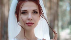 Πορτρέτο μιας νύφης σε ένα δάσος, σε ένα γαμήλιο φόρεμα που αγγίζει μια μπούκλα της τρίχας της, χαμόγελο, κινηματογράφηση σε πρώτ φιλμ μικρού μήκους