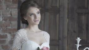 Πορτρέτο μιας νύφης στο γαμήλιο φόρεμα με τα λουλούδια σε ένα ηλιόλουστο πάρκο φιλμ μικρού μήκους