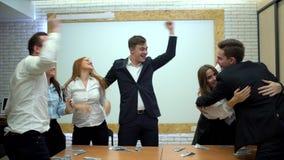 Πορτρέτο μιας ομάδας ευτυχών και διαφορετικών επιχειρησιακών νέων Πηδούν στον αέρα και την ευθυμία για να γιορτάσουν το τους απόθεμα βίντεο