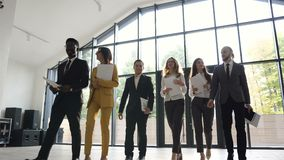 Πορτρέτο μιας ομάδας νέων multiethnic επιχειρηματιών που πηγαίνουν στη διάσκεψη στο σύγχρονο γραφείο επιχείρηση επιτυχής απόθεμα βίντεο