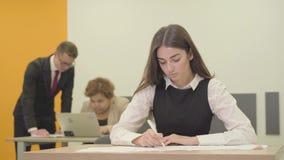 Πορτρέτο μιας πολυάσχολης νέας γυναίκας στην επίσημη ένδυση που γράφει σε χαρτί στο πρώτο πλάνο στο γραφείο ενώ το αρσενικό της κ φιλμ μικρού μήκους