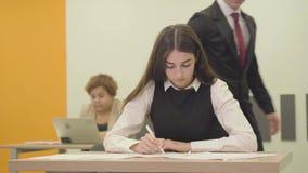 Πορτρέτο μιας πολυάσχολης νέας γυναίκας στην επίσημη ένδυση που γράφει σε χαρτί στο πρώτο πλάνο στο γραφείο ενώ το αρσενικό της κ απόθεμα βίντεο