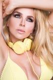 Πορτρέτο μιας πολύ όμορφης γυναίκας ξανθών μαλλιών στην προκλητική εξάρτηση με τα ακουστικά Στοκ Εικόνες