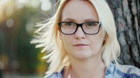 Πορτρέτο μιας σκεπτικής νέας γυναίκας στα γυαλιά Κοιτάζει έξω στην απόσταση, τα παιχνίδια αέρα με την τρίχα της Κάθεται στο α στοκ φωτογραφία με δικαίωμα ελεύθερης χρήσης