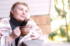 Πορτρέτο μιας σκεπτικής ώριμης γυναίκας με το φλυτζάνι του καυτού ποτού και στοκ φωτογραφία με δικαίωμα ελεύθερης χρήσης