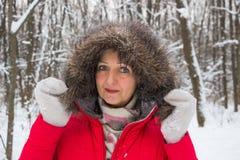 Πορτρέτο μιας συμπαθητικής ανώτερης γυναίκας στο ξύλο χειμερινού χιονιού στο κόκκινο παλτό Στοκ Εικόνα