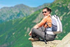 Πορτρέτο μιας συνεδρίασης γυναικών σε έναν βράχο στα βουνά με ένα BA Στοκ Φωτογραφία