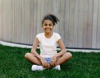 Πορτρέτο μιας συνεδρίασης κοριτσιών χαμόγελου στη χλόη Στοκ φωτογραφία με δικαίωμα ελεύθερης χρήσης
