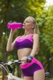 Πορτρέτο μιας φίλαθλης νέας γυναίκας σε ένα ποδήλατο, το οποίο πίνει wate Στοκ εικόνες με δικαίωμα ελεύθερης χρήσης