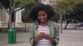 Πορτρέτο μιας χαμογελώντας αφρικανικής νέας γυναίκας που χρησιμοποιεί το smartphone απόθεμα βίντεο