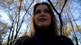 Πορτρέτο μιας χαμογελώντας γυναίκας που περιβάλλει στο πάρκο φθινοπώρου σε αργή κίνηση 4k 60fps Κορίτσι σε ένα παλτό που περπατά  φιλμ μικρού μήκους