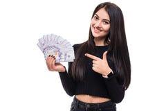 Πορτρέτο μιας χαμογελώντας νέας γυναίκας με τη μακριά τρίχα brunette που κοιτάζει και που δείχνει τα χρήματα μετρητών στο απομονω στοκ εικόνα