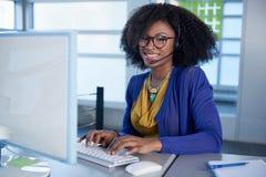 Πορτρέτο μιας χαμογελώντας εξυπηρέτησης πελατών αντιπροσωπευτικής με ένα afro στον υπολογιστή που χρησιμοποιεί την κάσκα Στοκ Εικόνες