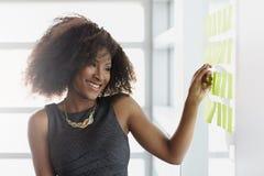 Πορτρέτο μιας χαμογελώντας επιχειρησιακής γυναίκας με ένα afro στο φωτεινό γραφείο γυαλιού Στοκ Φωτογραφίες