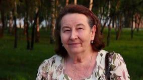 Πορτρέτο μιας χαμογελώντας ηλικιωμένης γυναίκας στο πάρκο φιλμ μικρού μήκους