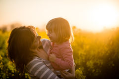 Πορτρέτο μιας χαμογελώντας μητέρας με το κοριτσάκι στο υπόβαθρο ηλιοβασιλέματος Στοκ φωτογραφία με δικαίωμα ελεύθερης χρήσης