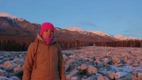 Πορτρέτο μιας χαμογελώντας νέας γυναίκας στο πόδι των βουνών στο ηλιοβασίλεμα απόθεμα βίντεο