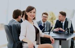 Πορτρέτο μιας χαρισματικής γυναίκας σε μια συνεδρίαση ενώ η ομάδα της που εργάζεται στο υπόβαθρο στοκ φωτογραφία