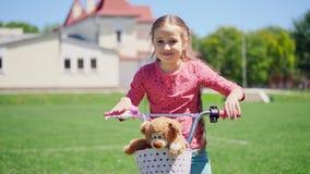 Πορτρέτο μιας χαριτωμένης συνεδρίασης μικρών κοριτσιών σε ένα ποδήλατο φιλμ μικρού μήκους