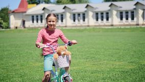 Πορτρέτο μιας χαριτωμένης συνεδρίασης μικρών κοριτσιών σε ένα ποδήλατο με το παιχνίδι απόθεμα βίντεο