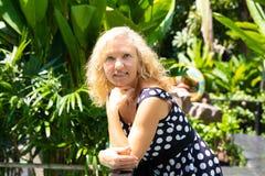 Πορτρέτο μιας 50χρονης γυναίκας το καλοκαίρι σε ένα κλίμα των πράσινων τροπικών φοινίκων στοκ φωτογραφία