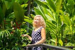 Πορτρέτο μιας 50χρονης γυναίκας το καλοκαίρι σε ένα κλίμα των πράσινων τροπικών φοινίκων στοκ φωτογραφίες