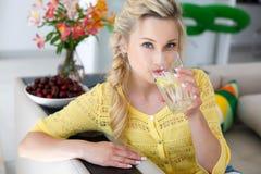 Πορτρέτο μιας όμορφης γυναίκας με ένα ποτήρι του νερού στην κουζίνα Στοκ Εικόνα