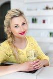 Πορτρέτο μιας όμορφης γυναίκας με ένα ποτήρι του νερού στην κουζίνα Στοκ φωτογραφία με δικαίωμα ελεύθερης χρήσης