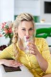 Πορτρέτο μιας όμορφης γυναίκας με ένα ποτήρι του νερού στην κουζίνα Στοκ Φωτογραφίες