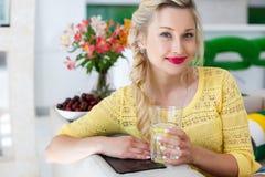 Πορτρέτο μιας όμορφης γυναίκας με ένα ποτήρι του νερού στην κουζίνα Στοκ Εικόνες