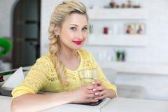 Πορτρέτο μιας όμορφης γυναίκας με ένα ποτήρι του νερού στην κουζίνα Στοκ φωτογραφίες με δικαίωμα ελεύθερης χρήσης