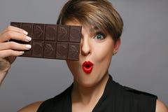 Πορτρέτο μιας όμορφης γυναίκας που είναι ένας πραγματικός ανεμιστήρας σοκολάτας σε ένα γκρίζο υπόβαθρο Στοκ Εικόνα