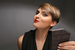 Πορτρέτο μιας όμορφης γυναίκας που είναι ένας πραγματικός ανεμιστήρας σοκολάτας σε ένα γκρίζο υπόβαθρο Στοκ φωτογραφία με δικαίωμα ελεύθερης χρήσης