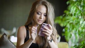 Πορτρέτο μιας όμορφης γυναίκας που εξετάζει το όργανο ελέγχου ενός κινητού τηλεφώνου περιμένοντας μια διαταγή σε ένα εστιατόριο φιλμ μικρού μήκους