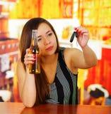Πορτρέτο μιας όμορφης γυναίκας που κρατά μια μπύρα με ένα χέρι και τα κλειδιά αυτοκινήτων της με την άλλο χέρι, στο υπόβαθρο φραγ Στοκ Φωτογραφία