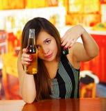 Πορτρέτο μιας όμορφης γυναίκας που κρατά μια μπύρα με ένα χέρι και τα κλειδιά αυτοκινήτων της με την άλλο χέρι, στο υπόβαθρο φραγ Στοκ φωτογραφία με δικαίωμα ελεύθερης χρήσης