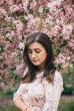 Πορτρέτο μιας όμορφης γυναίκας που στέκεται κοντά σε ένα ρόδινο ανθίζοντας δέντρο μηλιάς Στοκ φωτογραφία με δικαίωμα ελεύθερης χρήσης