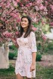 Πορτρέτο μιας όμορφης γυναίκας που στέκεται κοντά σε ένα ρόδινο ανθίζοντας δέντρο μηλιάς Στοκ Εικόνα