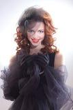 Πορτρέτο μιας όμορφης γυναίκας σε ένα αναδρομικό ύφος στο μαύρο φόρεμα στοκ φωτογραφία