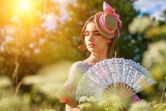 Πορτρέτο μιας όμορφης γυναίκας στα εκλεκτής ποιότητας ενδύματα με έναν ανεμιστήρα στη φύση μια ηλιόλουστη ημέρα στοκ φωτογραφία με δικαίωμα ελεύθερης χρήσης