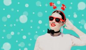 Πορτρέτο μιας όμορφης γυναίκας στην εξάρτηση Χριστουγέννων και των γυαλιών ηλίου με τα φωτεινά χρωματισμένα χείλια στοκ φωτογραφία