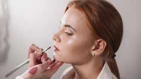 Πορτρέτο μιας όμορφης γυναίκας, στην οποία το κραγιόν εφαρμόζεται στα χείλια στο στούντιο απόθεμα βίντεο