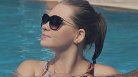 Πορτρέτο μιας όμορφης καυκάσιας γυναίκας AI μια πισίνα Όμορφη μακρυμάλλης χαλάρωση κοριτσιών στο μπλε νερό λιμνών απόθεμα βίντεο