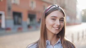 Πορτρέτο μιας όμορφης νέας γυναίκας που εξετάζει τη κάμερα και που χαμογελά τη στάση στο παλαιό υπόβαθρο οδών r απόθεμα βίντεο