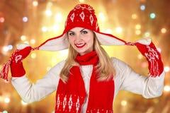 Πορτρέτο μιας όμορφης νέας γυναίκας σε ένα πλεκτό κόκκινο καπέλο, ένα μαντίλι και τα γάντια με μια διακόσμηση Χριστουγέννων στοκ εικόνα
