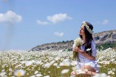 Πορτρέτο μιας όμορφης νέας γυναίκας στο chamomile τομέα Ευτυχές κορίτσι που συλλέγει τις μαργαρίτες Ένα κορίτσι που στηρίζεται σε στοκ φωτογραφίες με δικαίωμα ελεύθερης χρήσης