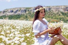 Πορτρέτο μιας όμορφης νέας γυναίκας στο chamomile τομέα Ευτυχές κορίτσι που συλλέγει τις μαργαρίτες Ένα κορίτσι που στηρίζεται σε στοκ εικόνες