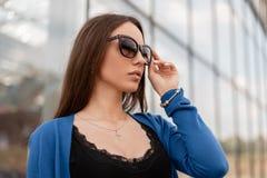 Πορτρέτο μιας όμορφης νέας γυναίκας hipster με τα προκλητικά χείλια σε ένα πλεκτό μπλε μοντέρνο ακρωτήριο σε μια μαύρη μοντέρνη μ στοκ εικόνες με δικαίωμα ελεύθερης χρήσης