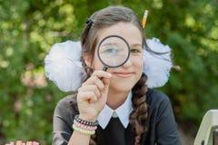 Πορτρέτο μιας όμορφης νέας μαθήτριας που εξετάζει μέσω μιας ενίσχυσης - γυαλί και του καθίσματος ένα γραφείο Στοκ Φωτογραφίες