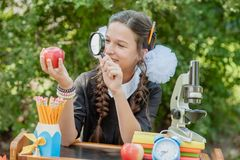 Πορτρέτο μιας όμορφης νέας μαθήτριας που εξετάζει μέσω μιας ενίσχυσης - γυαλί και του καθίσματος ένα γραφείο Στοκ Εικόνες